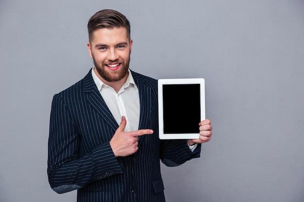 Retrato de um empresário sorridente apontando o dedo na tela do computador tablet, sobre a parede cinza