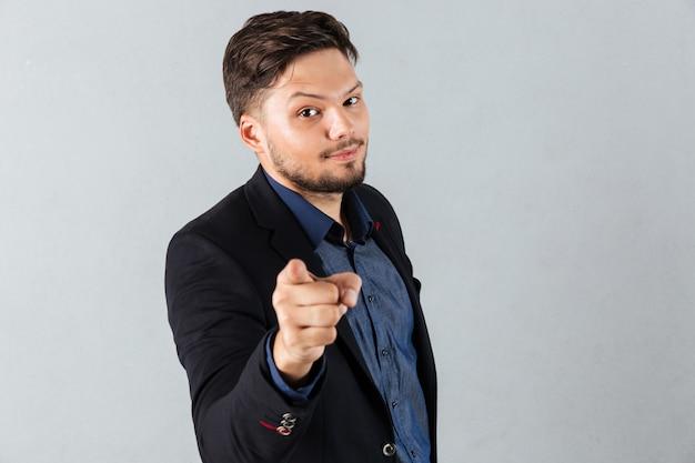 Retrato de um empresário sorridente apontando o dedo