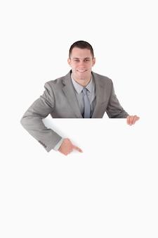 Retrato de um empresário sorridente apontando para algo