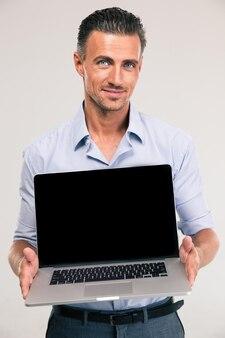 Retrato de um empresário sorridente mostrando a tela do laptop em branco isolada