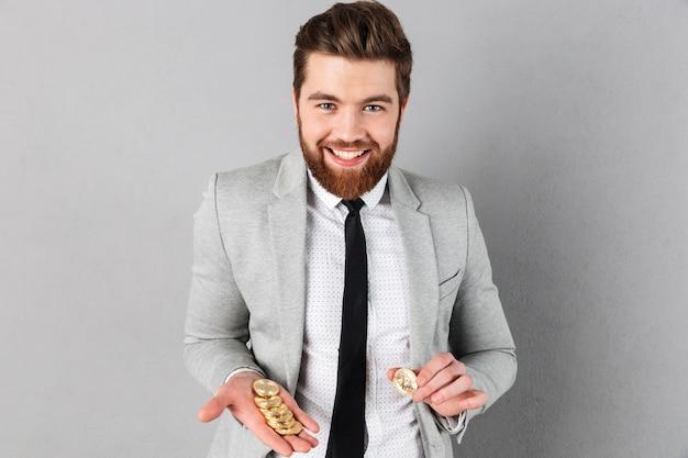 Retrato de um empresário sorridente mostrando bitcoins dourados