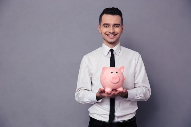 Retrato de um empresário sorridente segurando um mealheiro de porco na parede cinza