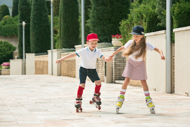 Retrato de um encantador casal adolescente patinando juntos de patins no parque. menino adolescente e menina caucasianos. roupas coloridas de crianças, estilo de vida, conceitos de cores da moda.