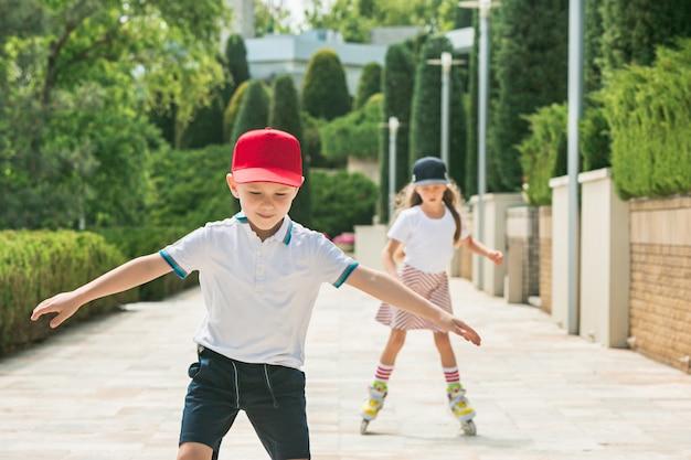 Retrato de um encantador casal adolescente patinando juntos de patins no parque. menino e menina adolescentes caucasianos