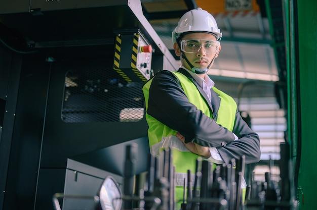 Retrato de um engenheiro barbudo usando um capacete dentro de uma fábrica industrial