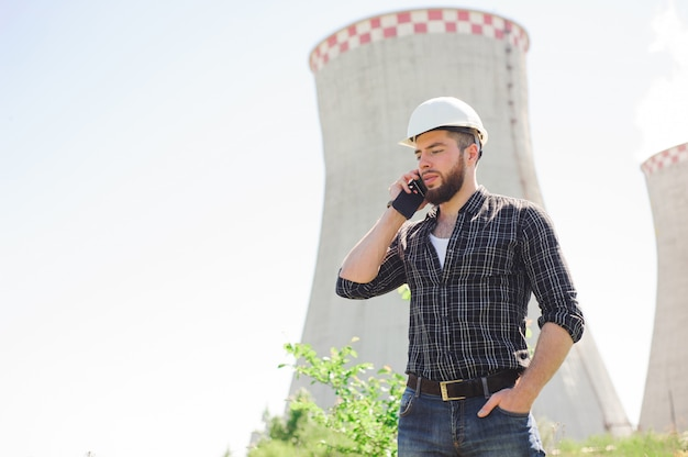 Retrato de um engenheiro bonito no trabalho com o telefone
