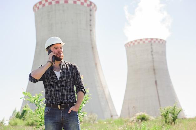 Retrato de um engenheiro bonito no trabalho com o telefone.