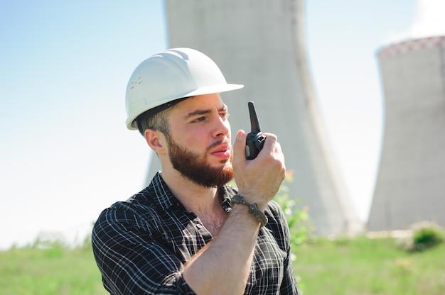 Retrato de um engenheiro construtor com um aparelho de rádio na mão.