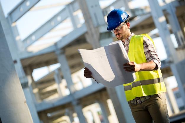 Retrato de um engenheiro de construção civil com capacete segurando um papel de impressão azul no canteiro de obras.