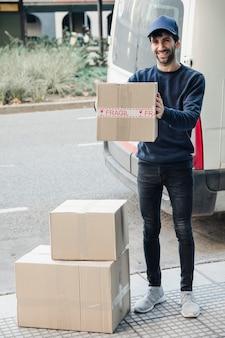 Retrato, de, um, entrega feliz, homem, com, caixa papelão, perto, veículo