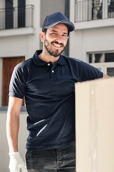 Retrato, de, um, entrega feliz, homem, com, caixa papelão