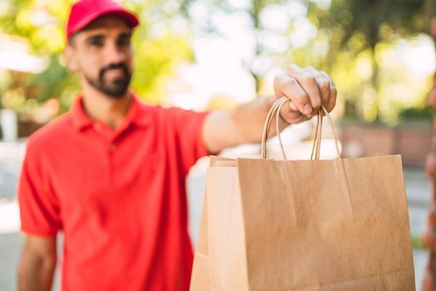 Retrato de um entregador carregando pacotes ao fazer entrega em domicílio para seu cliente. entrega e conceito de envio.