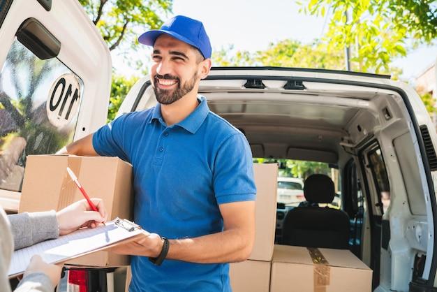 Retrato de um entregador carregando pacotes enquanto o cliente coloca a assinatura na área de transferência. entrega e conceito de envio.