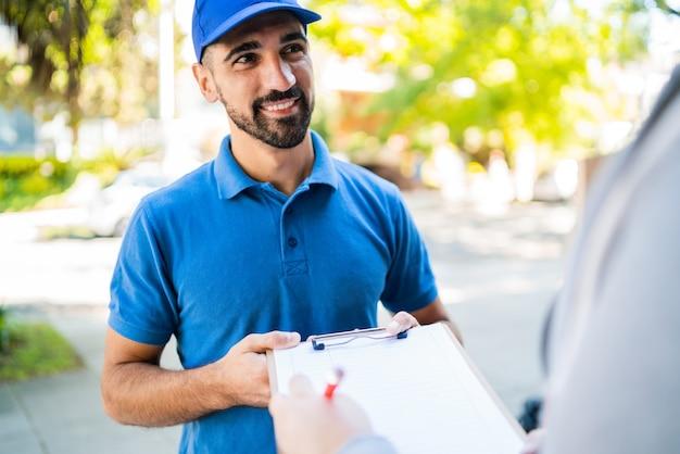 Retrato de um entregador carregando pacotes enquanto o cliente coloca a assinatura na prancheta