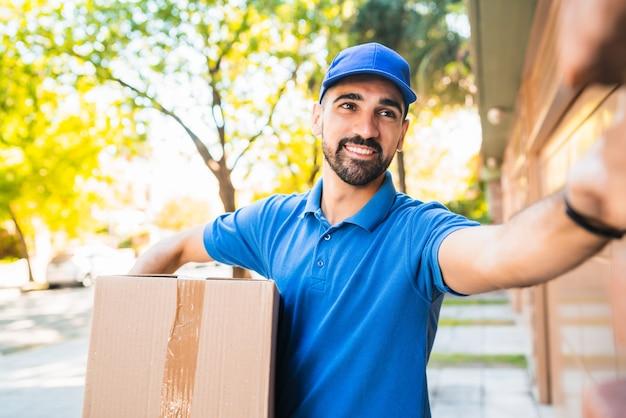 Retrato de um entregador carregando pacotes enquanto toca a campainha para fazer entrega em domicílio ao seu cliente. entrega e conceito de envio.