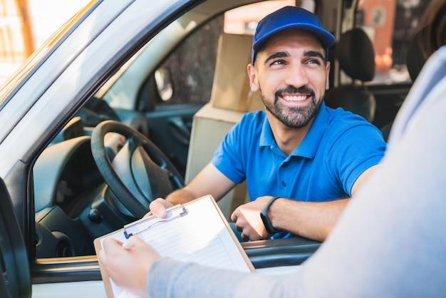 Retrato de um entregador na van enquanto o cliente colocava a assinatura na área de transferência. entrega e conceito de envio.