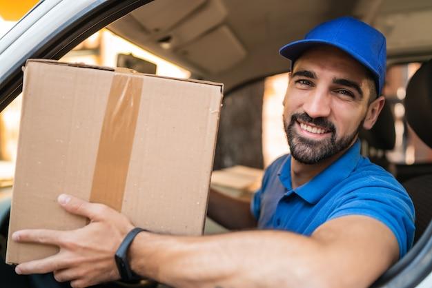 Retrato de um entregador segurando caixas de papelão na van. serviço de entrega e conceito de transporte.