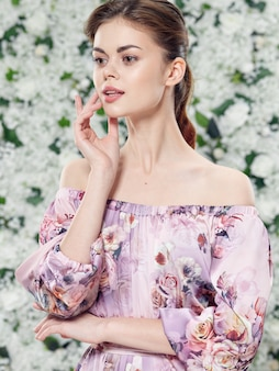 Retrato de um espaço de mulher jovem e bonita de flores em um vestido floral