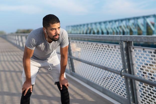Retrato de um esportista bonito com fones de ouvido, fazendo uma pausa no treino