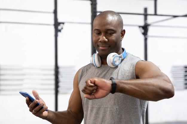 Retrato de um esportista masculino afro-americano, olhando para o relógio de pulso. conceito de tecnologia no esporte. foco seletivo.