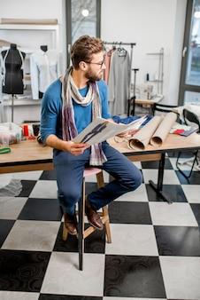 Retrato de um estilista bonito sentado com esboços de roupas no estúdio cheio de ferramentas de alfaiataria e roupas