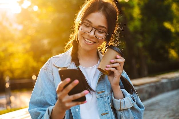 Retrato de um estudante adolescente jovem alegre positivo caminhando ao ar livre no belo parque verde, bebendo café usando telefone celular.