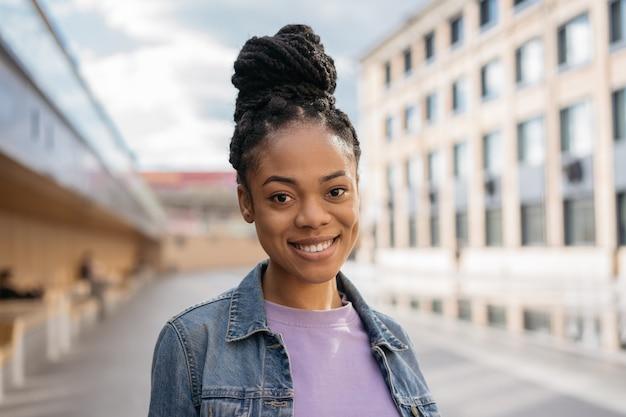 Retrato de um estudante afro-americano sorridente em pé no campus da universidade conceito de educação