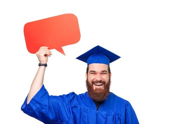 Retrato de um estudante alegre com barba, usando chapéu de solteiro, chapéu de formatura e segurando um balão de fala
