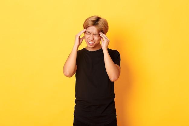 Retrato de um estudante asiático com problemas, tendo dor de cabeça, fazendo caretas de dor e tocando a cabeça, sofrendo de enxaqueca.