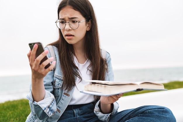 Retrato de um estudante confuso descontente emocional jovem bonita usando óculos, caminhando ao ar livre, lendo o livro usando o telefone celular.