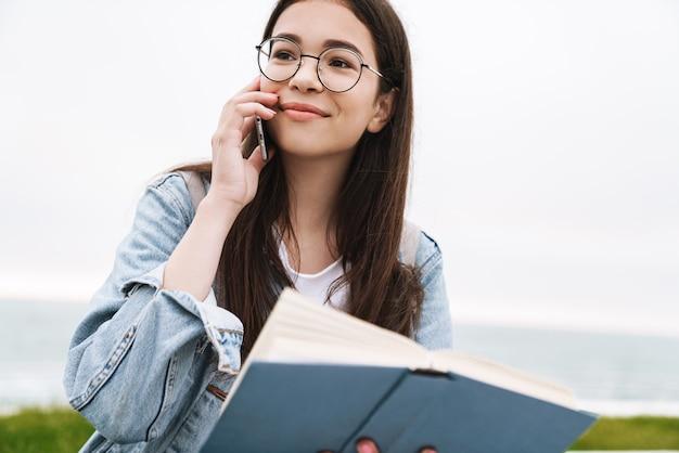 Retrato de um estudante de mulher bonita jovem emocional alegre de óculos, caminhando ao ar livre, lendo um livro falando por telefone celular.
