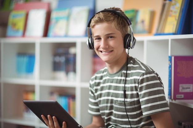 Retrato de um estudante feliz ouvindo música enquanto usa o tablet digital na biblioteca