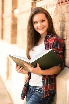 Retrato de um estudante fêmea de sorriso novo perto da parede.