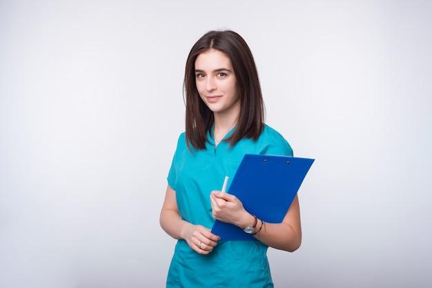 Retrato de um estudante jovem médico ou dentista segurando uma placa de papel azul no espaço em branco.