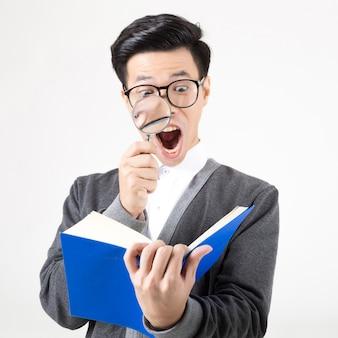 Retrato de um estudante novo de asiagraduate que guarda a lupa para ler o livro.