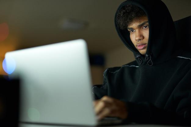 Retrato de um estudante ocupado estudando, trabalhando em um laptop, sentado em casa tarde da noite