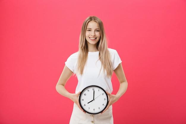 Retrato, de, um, excitado, menina jovem, vestido branco, t-shirt, apontar, despertador