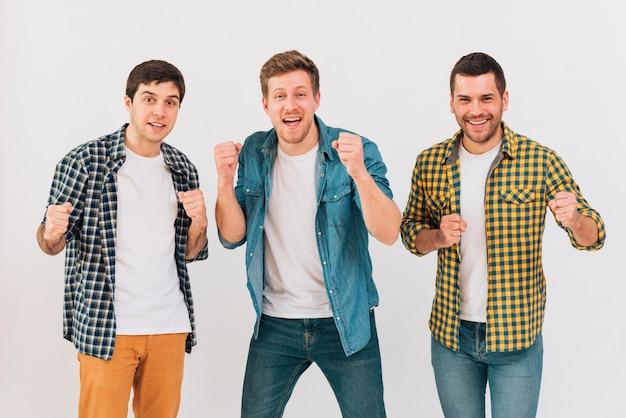 Retrato, de, um, excitado, sorrindo, homens jovens, cerrando, seu, punho, contra, parede branca