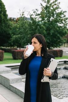 Retrato, de, um, executiva, com, laptop, café bebendo