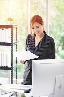 Retrato de um executivo feliz vestindo terno trabalhando em uma mesa no escritório, com a luz do sol.