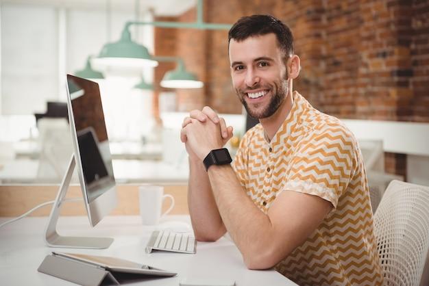 Retrato de um executivo sorridente, sentado à mesa