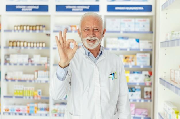 Retrato de um farmacêutico, mostrando um sinal de aprovação com a mão. um homem de cabelos grisalhos, de uniforme branco e gesticulando em aprovação com uma das mãos. olhe para a câmera, rosto sorridente