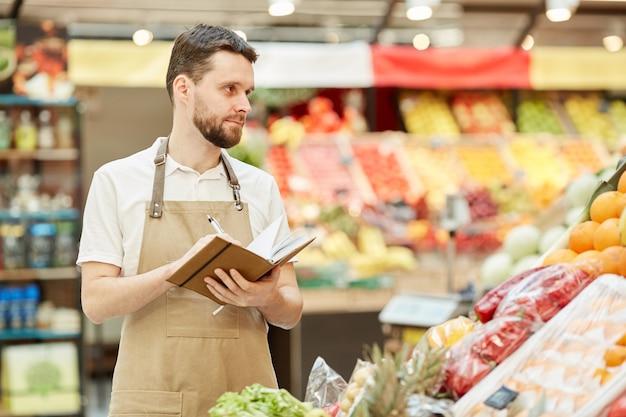 Retrato de um fazendeiro barbudo segurando um caderno enquanto vende frutas e vegetais frescos em uma barraca de mercado