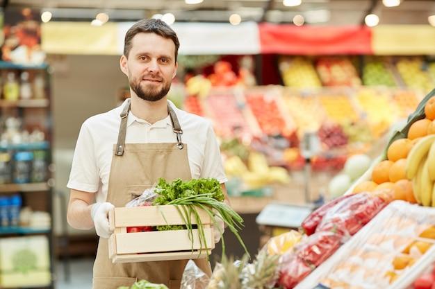 Retrato de um fazendeiro barbudo segurando uma caixa de vegetais enquanto vende produtos frescos na barraca do mercado
