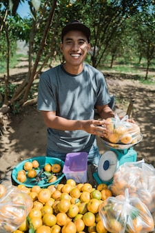Retrato de um fazendeiro feliz vendendo frutas de laranja
