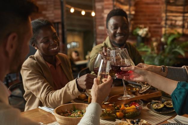 Retrato de um feliz casal afro-americano tilintando copos enquanto desfruta de um jantar com amigos e família em um interior aconchegante