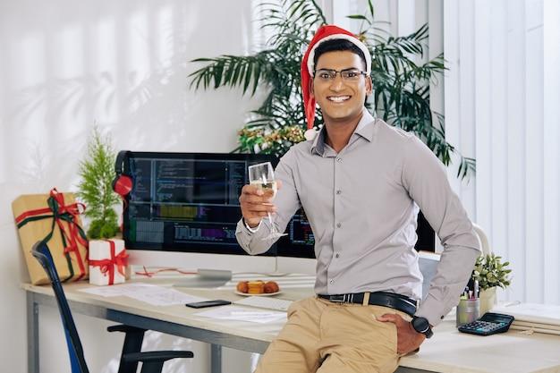 Retrato de um feliz desenvolvedor de software indiano sentado na mesa do escritório com uma taça de champanhe e comemorando o natal