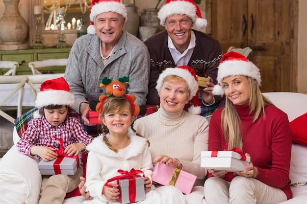 Retrato, de, um, feliz, família estendida, em, chapéu santa, prendendo presentes