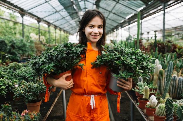 Retrato, de, um, feliz, femininas, jardineiro, segurando, dois, potted, plantas