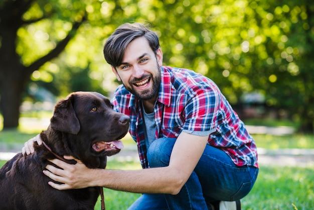 Retrato, de, um, feliz, homem jovem, com, seu, cão, parque